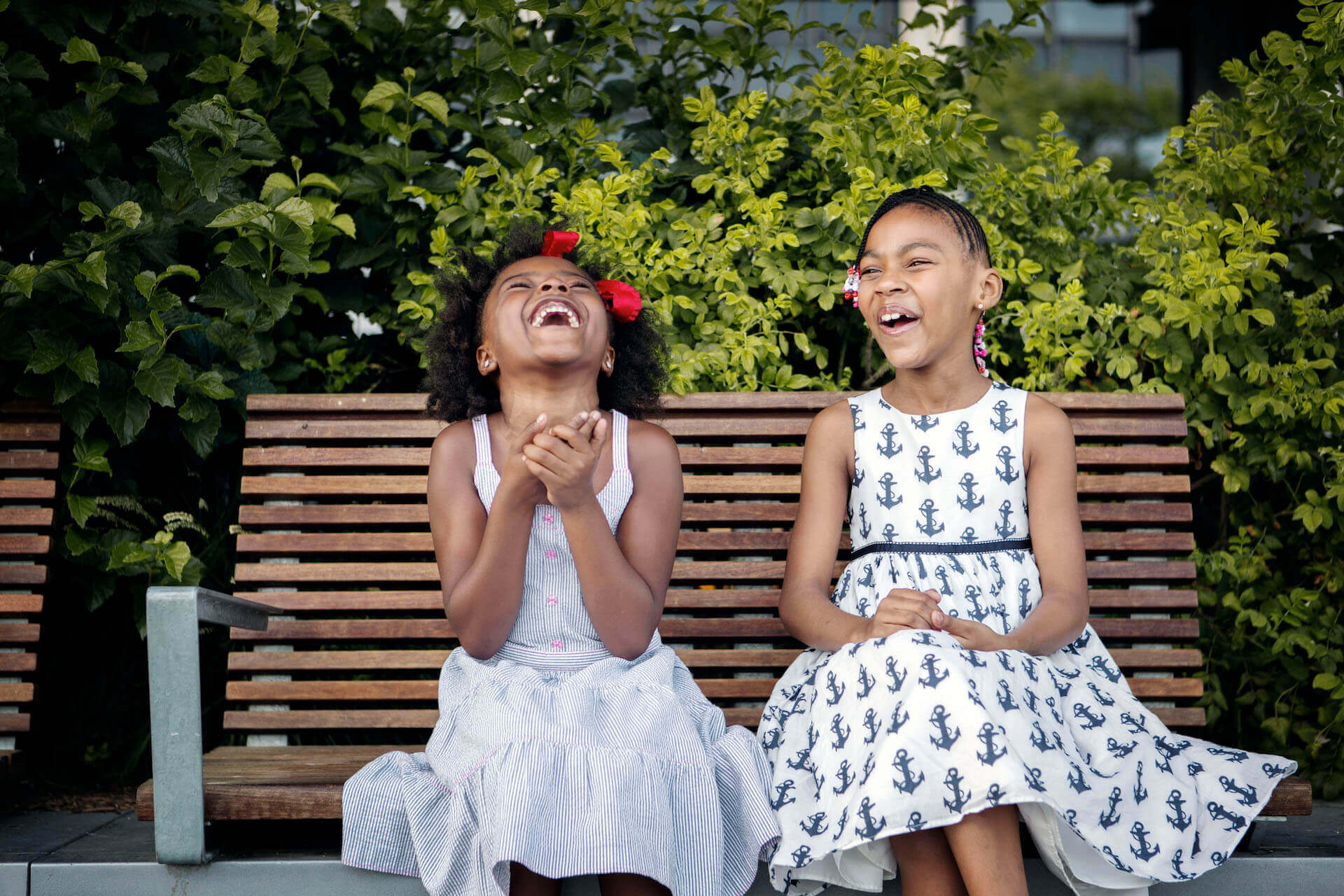 Two girls laughing on a bench