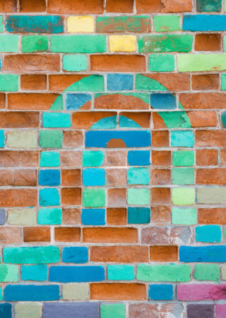 CHN Housing logo in a colorful pattern on a brick wall.