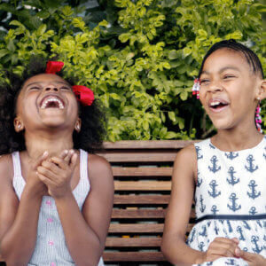 Two girls on a bench laughing